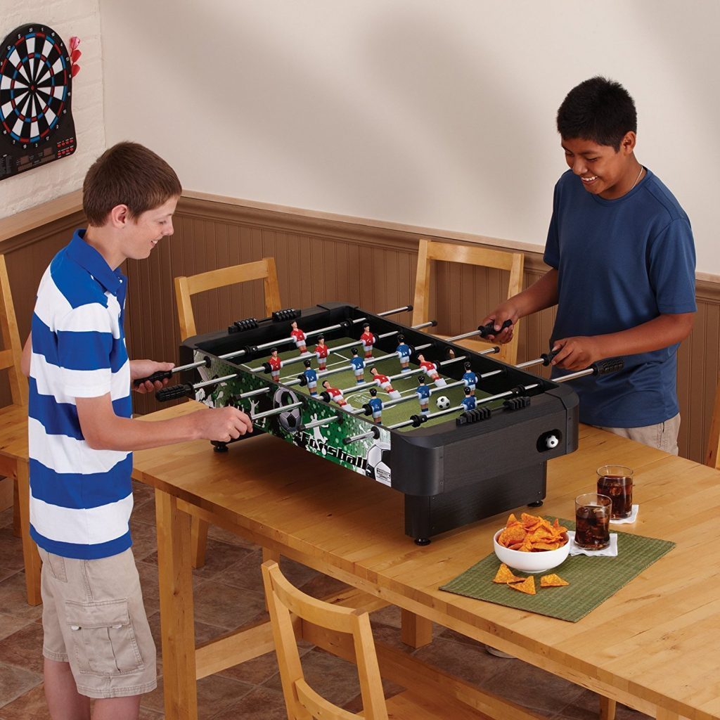 2-kids-playing-with-a-mini-foosball-table